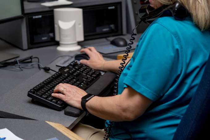 Individual answers a phone while typing on a computer.
