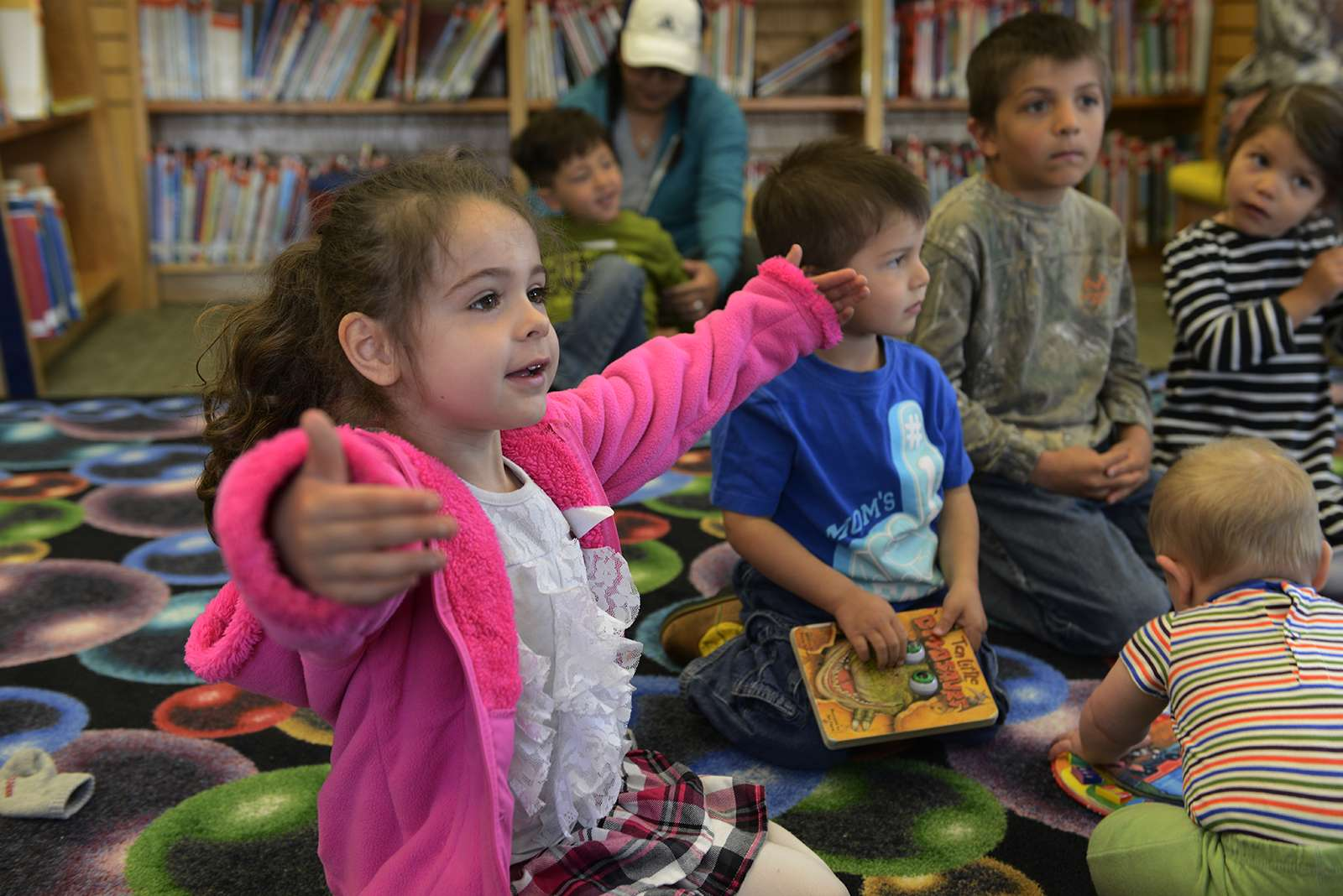 Young girl opens her arms wide during a sign language class
