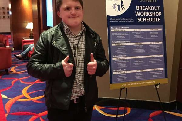 A teen with his thumbs up in front of a conference poster